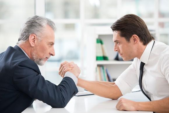Two businessmen arm wrestle.