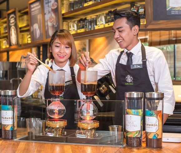 Starbucks employees in Cambodia prepare espresso.