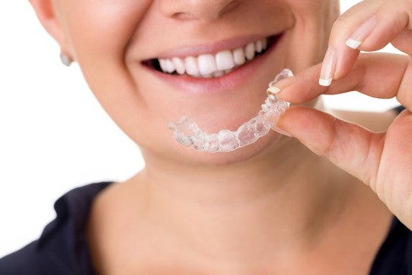 Smiling woman holding clear dental aligner