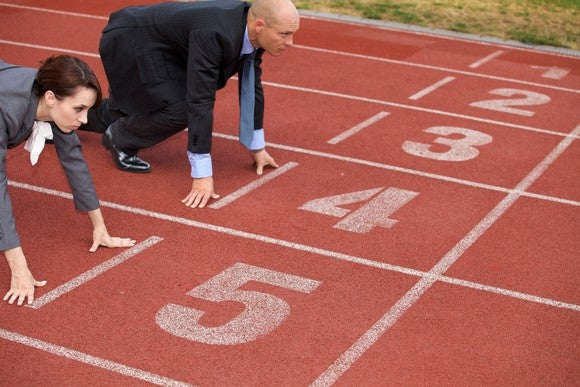 A businessman and woman crouch in starting position at the start of a running track.
