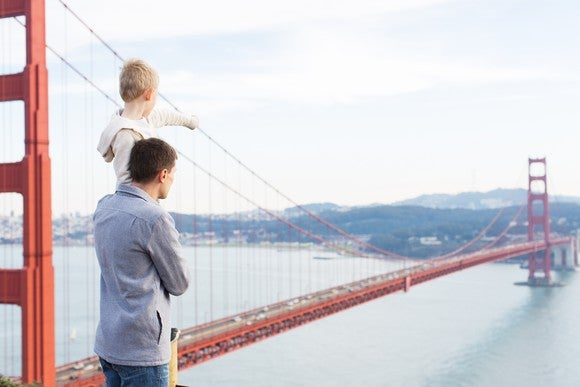 A man holds up a child, who points in the direction of the Golden Gate Bridge.