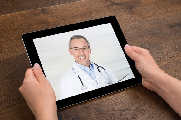 Two hands holding a tablet with a happy doctor on its screen