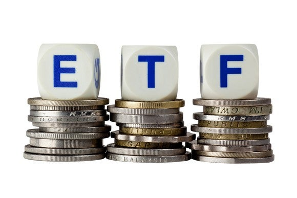 "Three dice spelling ""ETF"" on top of stacks of coins"