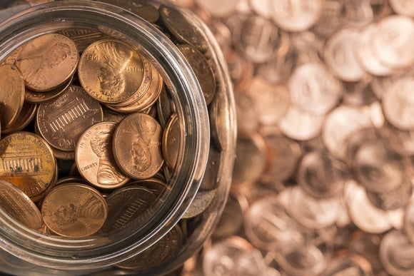 A jar of copper pennies surrounded by pennies.