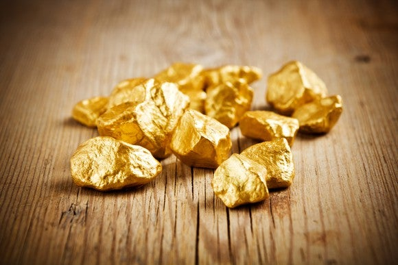Gold nuggets on a wooden table.
