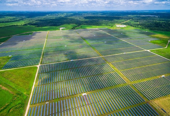 An aerial view of large solar farm in grassy area.