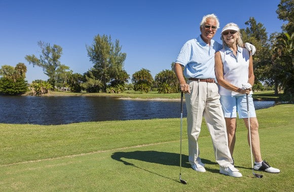 An elderly couple, both in sunglasses, stand holding clubs on a golf course, with a waterway, trees, and a blue sky behind them.