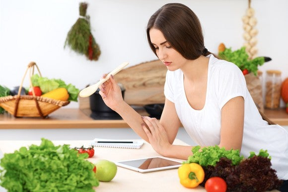 A woman, surrounded by fresh food in a kitchen and holding a wooden spoon in her hand, looks down at a tablet at the countertop.