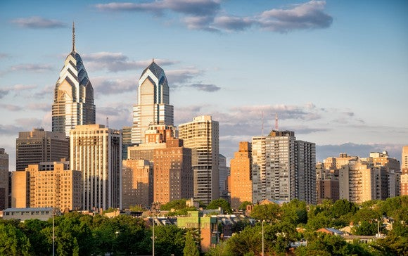 The Philadelphia skyline, with green trees in the foreground and a partly cloudy sky in the background.