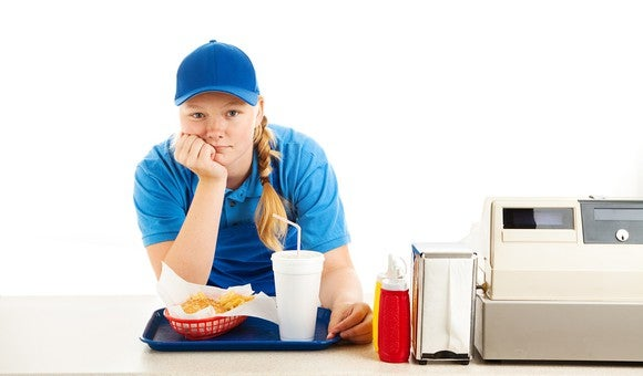 A frustrated-looking fast-food worker in a blue shirt and ball cap leans on the counter with her chin resting on the palm of her hand. Next to her are a cash register, a napkin dispenser, and condiments. In front of her is a tray with a fast-food order on it.