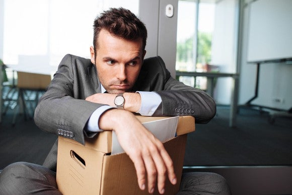 Young businessman with desk belongings packed into cardboard box