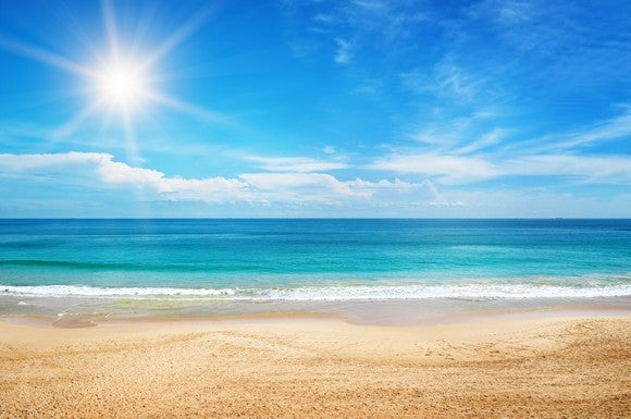 A beach with the sun shining in the background.