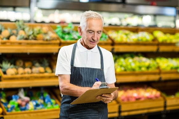 In a grocery-store setting, a gray-haired man in a short-sleeved shirt and apron writes on a clipboard.