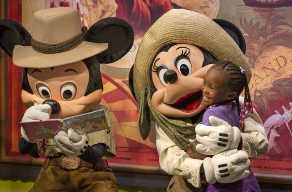 Mickey and Minnie Mouse greet a young child.