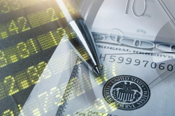$100 bill and pen superimposed onto stock board