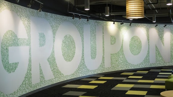 Curved, light green mosaic wall with Groupon's company name in large, white capital letters.