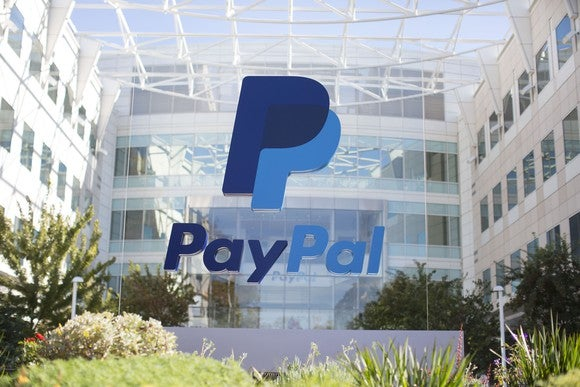 PayPal logo on transparent visage in front in courtyard.