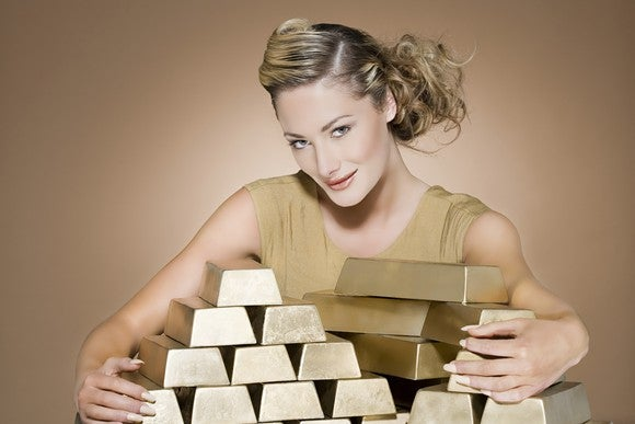 A woman wraps her arms around a stack of gold bars.