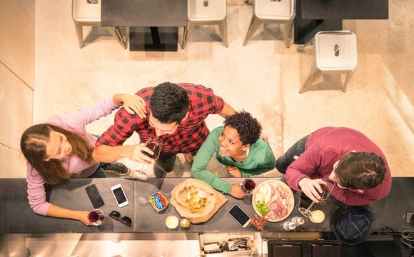 Overhead shot of friends eating and drinking wine with mobile devices on bar.