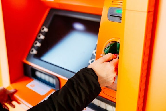 Hand inserting card into brightly colored orange ATM machine.