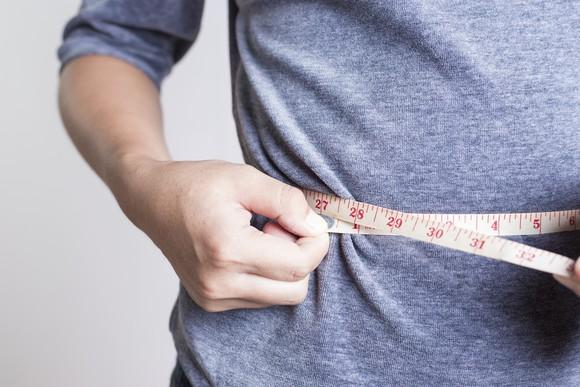 Person checking their waistline.