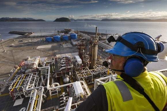 A man wearing blue ear protection, a blue hard hat, and a yellow vest, looking over oil and gas processing plant.
