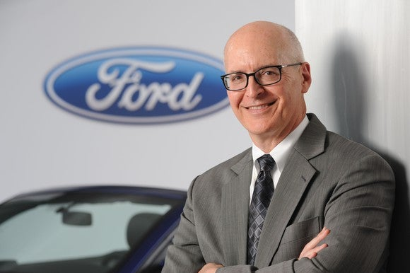 Ford's chief financial officer, Bob Shanks, standing with a Ford logo in the background.