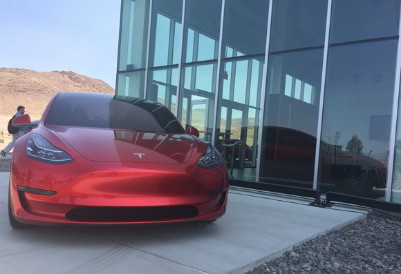 A red Model 3 prototype next to a glass building