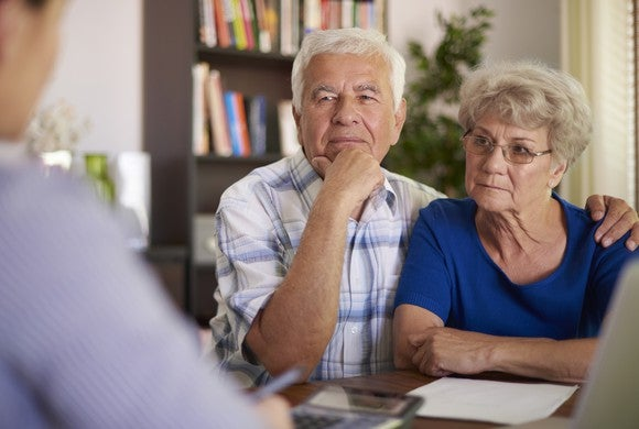 Older couple discussing finances, looking serious