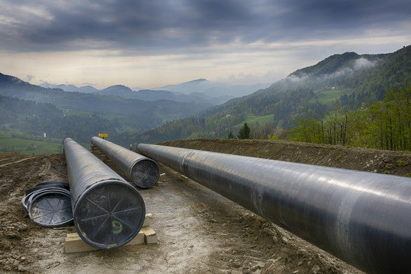 A pipeline construction site with mountains in the background.