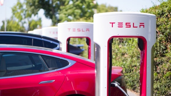 Red Tesla Model S charging at a Tesla Supercharger location