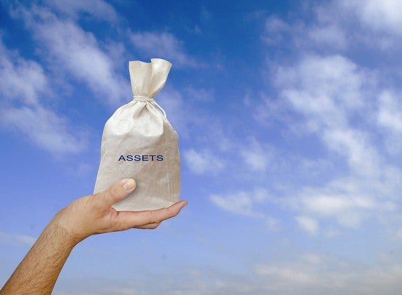 "A hand holds up a bag labeled ""assets"" against a cloudy sky."