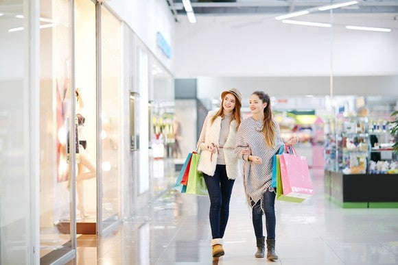 Two young women shop in a mall.