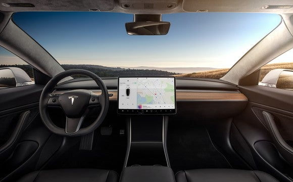 A Model 3's minimalist wood-grained dash and central touchscreen.