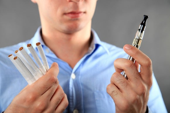 A young man deciding between cigarettes and an electronic cigarette.
