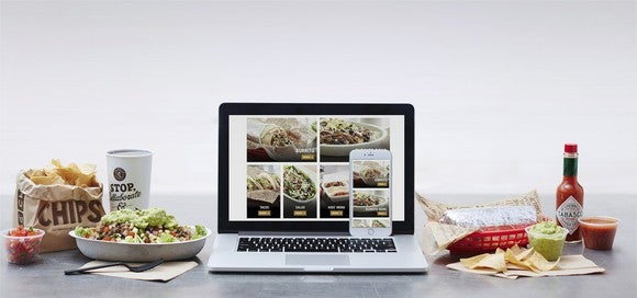 An assortment of Chipotle menu items are spread out on a tabletop. Between them sit a laptop and smartphone showing Chipotle's app.