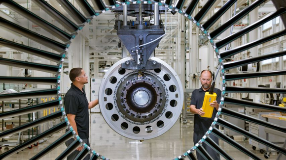 Two workers stand around a geared turbofan