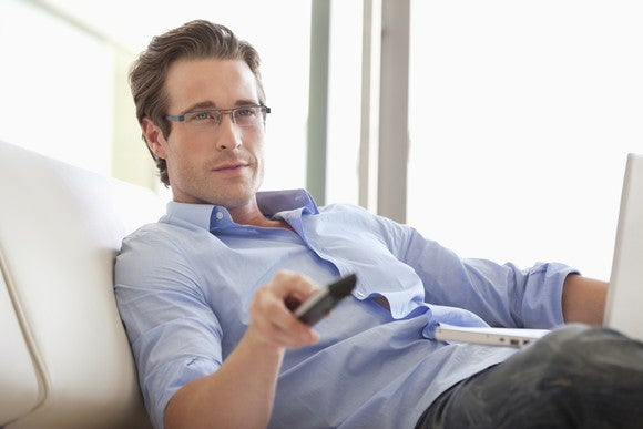A man holding a TV remote and looking forward.