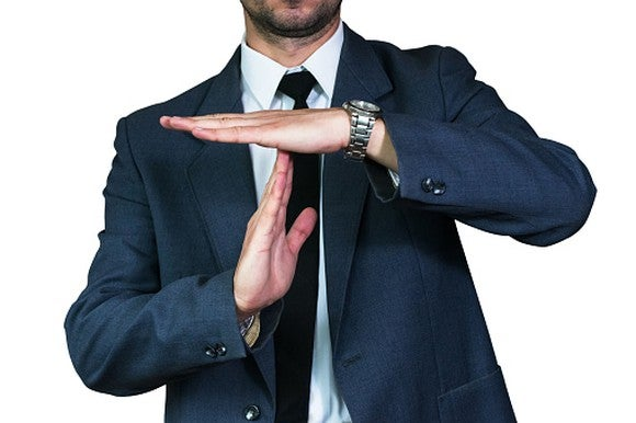 "man in a suit creating a ""T"" with his hands"