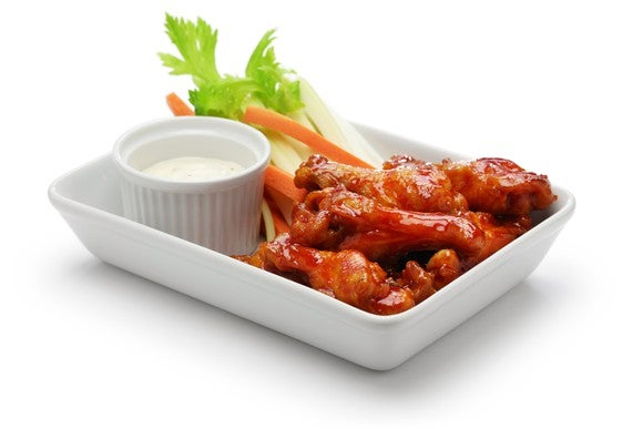 A plate of Buffalo chicken wings, celery, and ranch dressing.