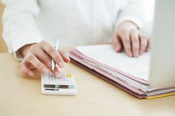 Woman looking over documents and using a calculator.
