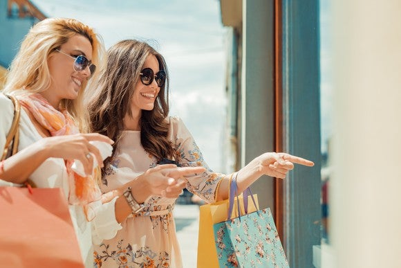 Two women holding shopping bags and pointing at a store window