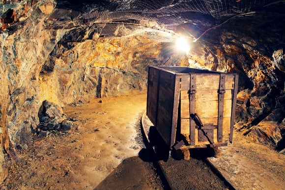 Wooden cart on rail track in gold mine