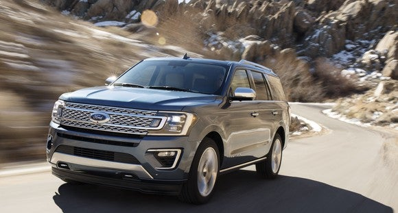 A 2018 Ford Expedition SUV in gray, on a winding mountain road.