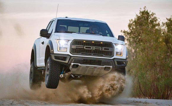 2017 Ford F-150 Raptor in white, on a dirt road with dust raised.