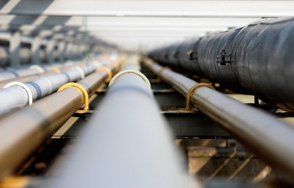 A head-on view of oil pipelines disappearing into the distance.