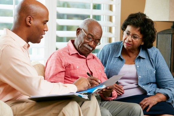 Older couple and younger male reviewing a contract