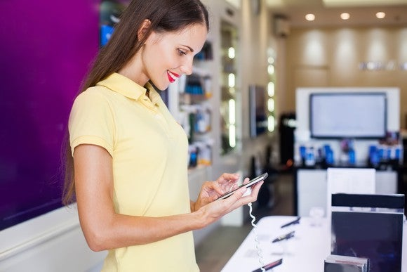 Smiling woman looking at phones by a store counter.