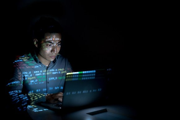 A man sitting in front of a computer in a dark room with the screen reflecting off him.