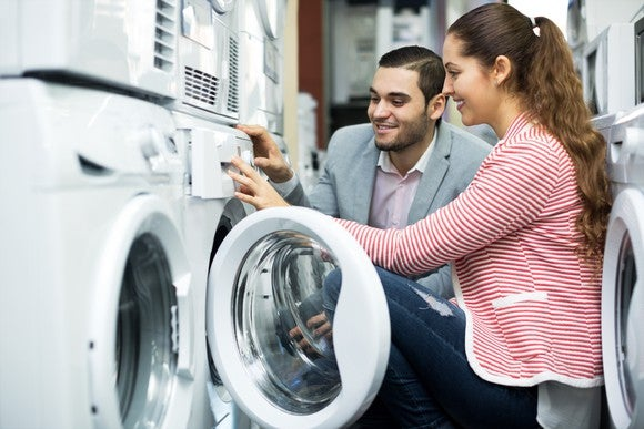 A woman and a man kneel near a dryer